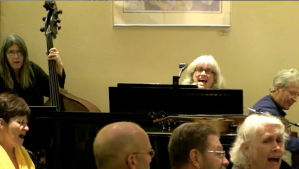 Suz at piano leading singlaong at memorial service